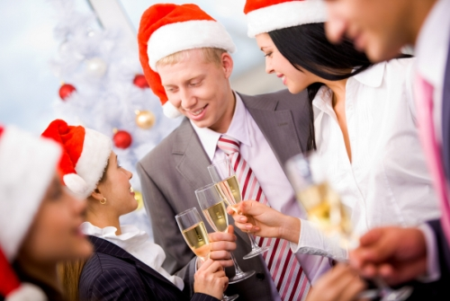 Image of cheering friends in Santa caps making toast at corporate party