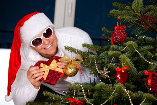 Santa Claus with a Christmas presents near christmas tree