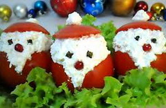 10 средних круглых помидоров, 150 г сыра, 5 яиц, 3 зубчика чеснока, майонез, соль (по вкусу), 10 ягод клюквы, 22 горошины черного перца или 20 соцветий гвоздики.  У помидоров срежьте шляпку, чайной ложкой выньте мякоть, посолите помидоры внутри.  Яйца отварите, очистите, натрите на мелкой терке. Смешайте с натертым сыром, измельченным чесноком, заправьте майонезом.  Нафаршируйте этой смесью помидоры, прикройте шляпками, нарисуйте бороду и помпон с помощью майонеза, обозначьте клюковкой нос, гвоздикой или горошинками перца - глаза.