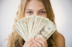 Girl (12-13) holding money fan against her face